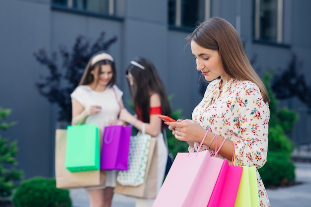Vendita, consumismo, tecnologia e concetto di persone - giovani donne felici con smartphone e borse della spesa.