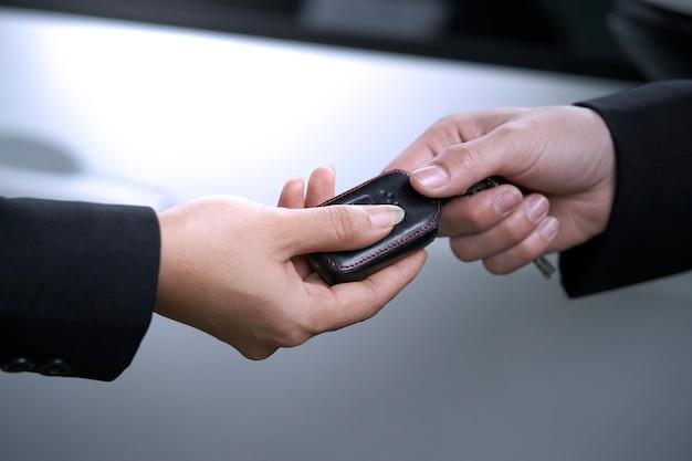 Vendita di auto in showroom, venditore consegna le chiavi al compratore dopo l'acquisto di una nuova auto.