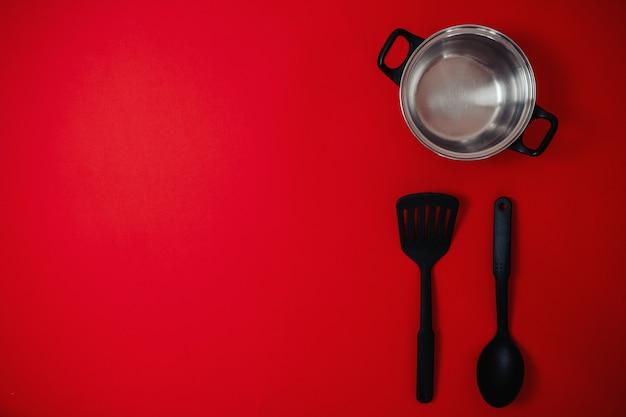 Vendita nera venerdì piatto lay, banner per negozio di articoli per la casa, pentola d'argento, spatola, cucchiaio grande sulla superficie rossa,