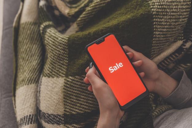 Vendita sullo schermo del telefono. la donna tiene un telefono in mano e vede la vendita di iscrizione. shopping online senza uscire di casa durante la quarantena. vendita venerdì nero