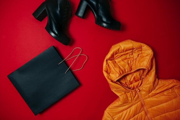 Vendita venerdì nero piatta, borsa venerdì nera, stivali, giacca gialla sulla superficie rossa,