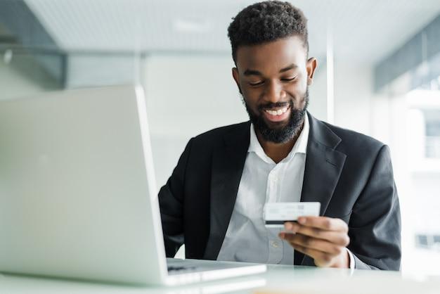 Vendite bancarie su internet. riuscito uomo d'affari africano che si siede ad un computer portatile e che tiene la carta di credito a disposizione fino a quando l'uomo d'affari che fa gli ordini tramite internet