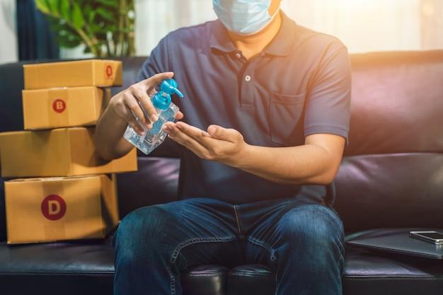 Vendite online dell'uomo asiatico che si lavano le mani con il gel dell'alcool. il venditore prepara la scatola di consegna per il cliente o l'e-commerce. il concetto impedisce la diffusione dei germi ed evita le infezioni covid-19