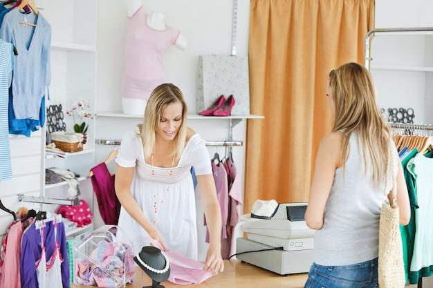 Venditore amichevole che imballa i vestiti in un sacchetto