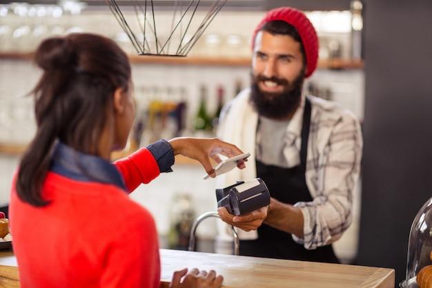 Venditore che prende pagamento con il lettore e lo smartphone della carta di credito