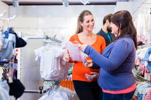 Venditore con le coppie che comprano i vestiti del bambino in negozio