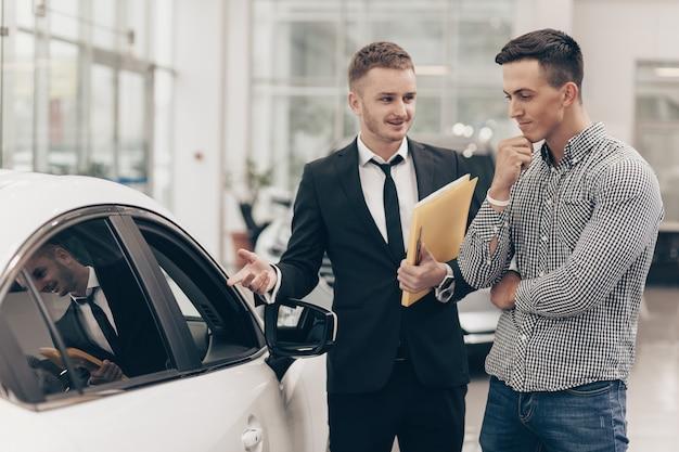 Venditore di auto che lavora con un cliente presso il concessionario