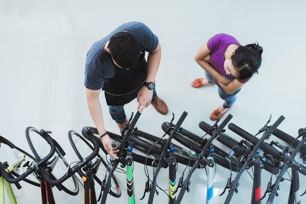 Venditore di biciclette aiutare i clienti a comprare una bici in un negozio