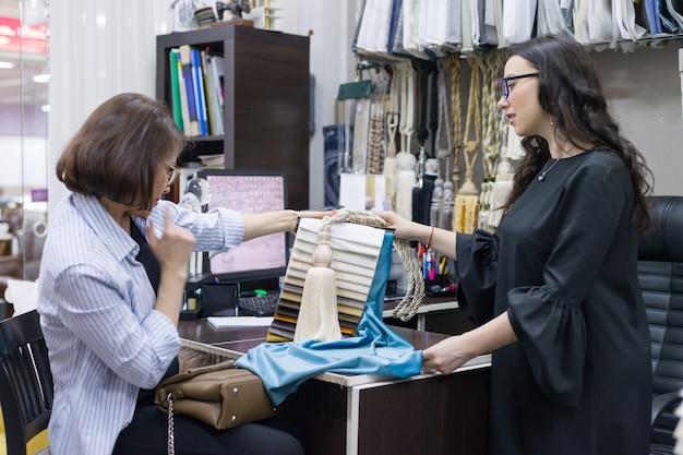 Venditore femminile che parla con il compratore in negozio di tessuti e accessori per tende