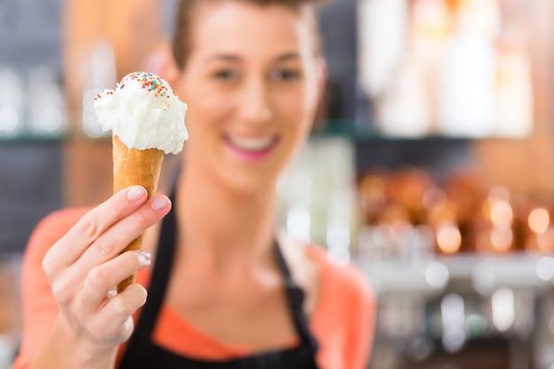 Venditore femminile in salone con cono gelato
