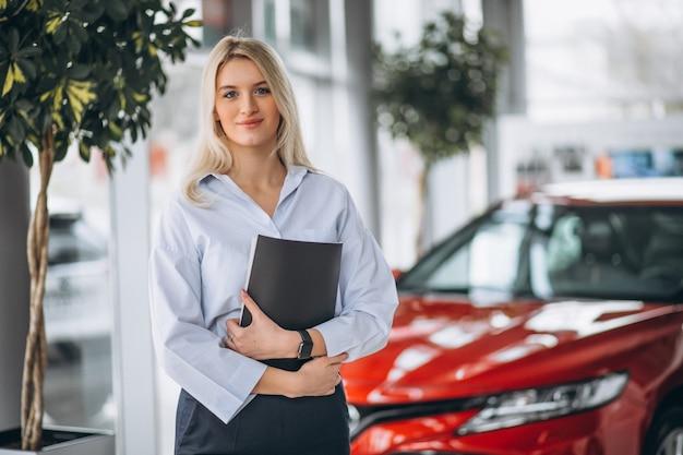 Venditore femminile in una sala d'esposizione dell'automobile