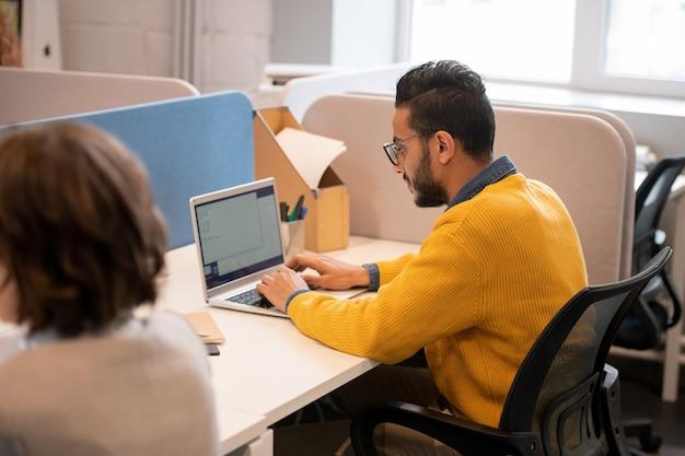 Venditore mediorientale giovane e occupato serio in maglione giallo che si siede sulla sedia girevole e che compone il piano di vendita sul computer portatile