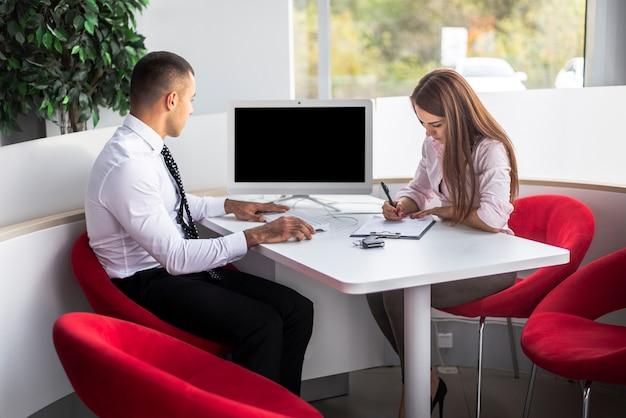 Venditori del commerciante di automobile di vista frontale all'ufficio che fa lavoro di ufficio