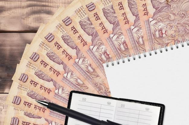 Ventaglio di banconote da 10 rupie indiane e blocco note con rubrica e penna nera. concetto di pianificazione finanziaria e strategia aziendale. contabilità e investimenti