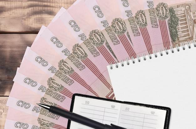 Ventaglio di banconote da 100 rubli russi e blocco note con rubrica e penna nera. concetto di pianificazione finanziaria e strategia aziendale. contabilità e investimenti