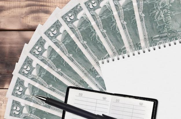 Ventilatore di banconote da 2 dollari usa e blocco note con rubrica e penna nera. concetto di pianificazione finanziaria e strategia aziendale.