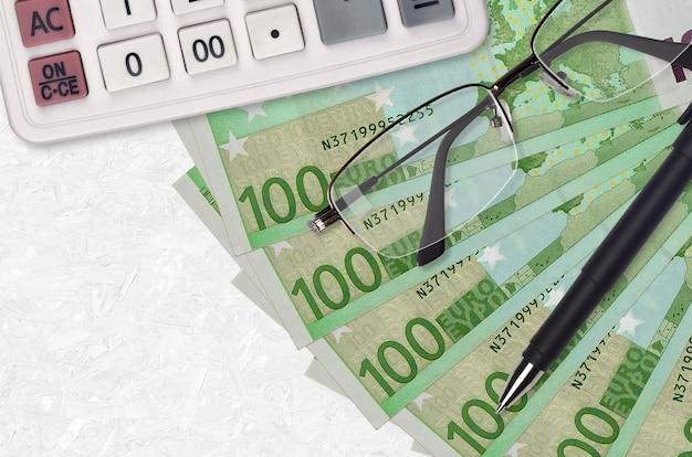Ventilatore di fatture di 100 euro e calcolatrice con occhiali e penna