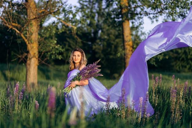 Vento soffia vestito viola donna incinta mentre lei sta nel campo di lavanda
