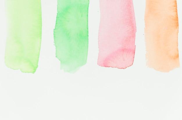 Verde; tratto di pennello rosso e arancione su sfondo di carta bianca