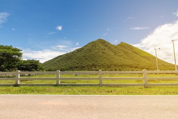 Verdi colline e recinto erba rigogliosa, cielo blu con nuvole bianche