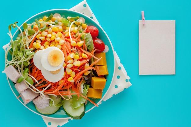Verdura di insalata fresca con l'uovo di pollo bollito e carta per appunti in bianco su fondo blu