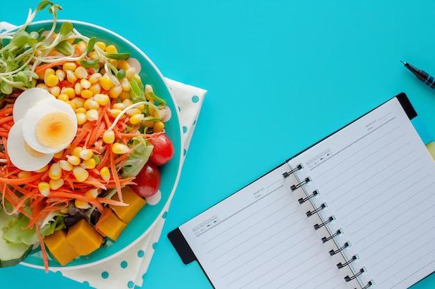 Verdura di insalata fresca con l'uovo di pollo bollito, taccuino a spirale in bianco e una penna su fondo blu