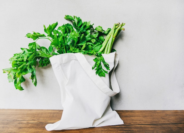 Verdura fresca biologica in borse di tessuto di cotone eco sul tavolo di legno