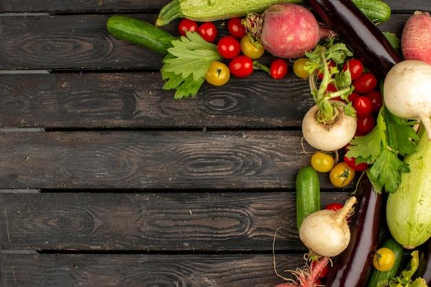 Verdura fresca colorata su un pavimento di legno marrone