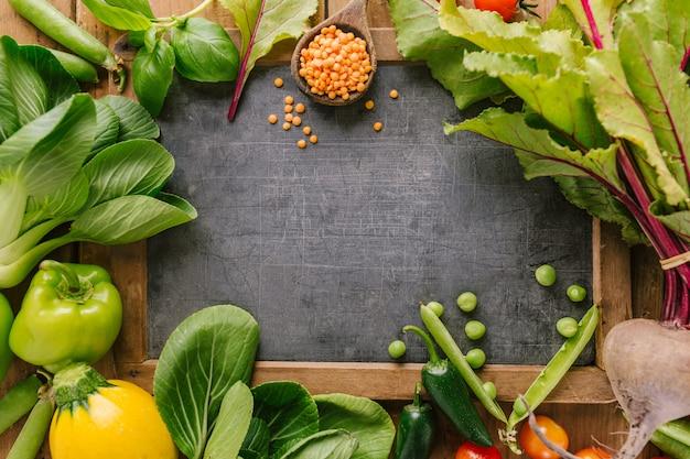 Verdura fresca con la scheda sulla tabella di legno