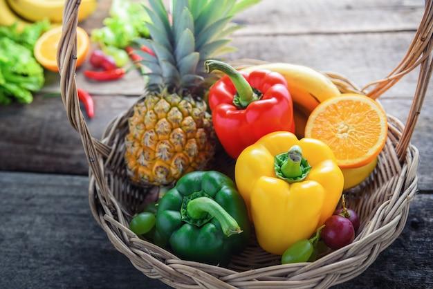 Verdura fresca e frutta per la cena di forma fisica su fondo di legno, concetto dell'alimento