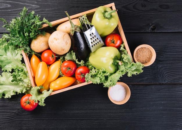 Verdura fresca in contenitore e spezie su fondo di legno nero