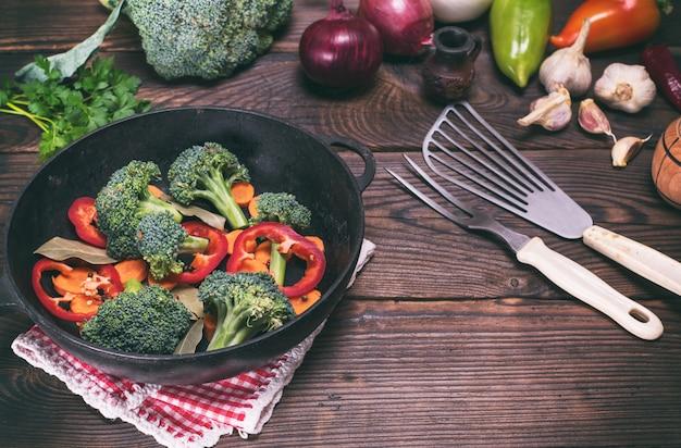 Verdura fresca in una padella nera in ghisa