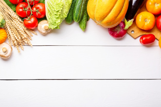 Verdura fresca organica cruda assortita sulla tavola di legno bianca. cucina vegetariana fresca da giardino.
