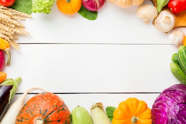 Verdura fresca organica cruda assortita sulla tavola di legno bianca.