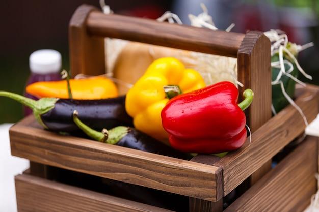 Verdura fresca, peperoni, melanzane in una scatola di legno su un ceppo all'aperto nel giardino.