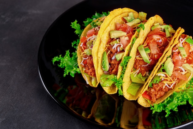 Verdura fresca sui tacos deliziosi sulla banda nera su fondo di legno