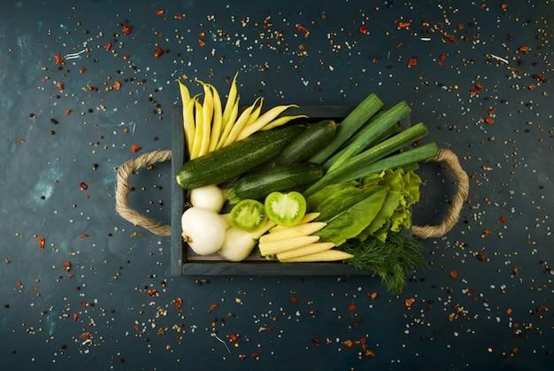 Verdura fresca sulla scatola di legno su una pietra scura. il concetto di vintage. le giovani cipolle di aspetto di vernice verde di pomodoro su una superficie scura.