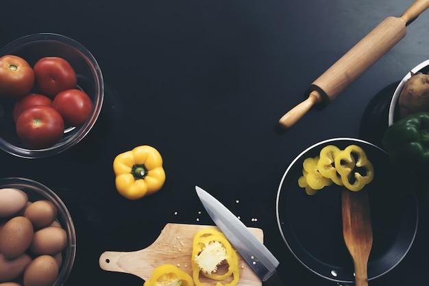 Verdura fresca, uova e peperone a pezzi che taglia a pezzi su fondo di legno nero.