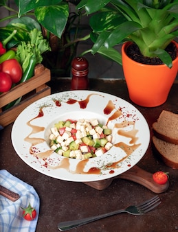 Verdura, pomodori, cetrioli, insalata di roka. insalata con sumakh e limone sul tavolo della cucina all'interno del piatto bianco