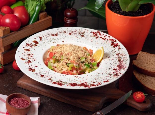 Verdura, pomodori, insalata di cetrioli con cracker. insalata sul tavolo della cucina all'interno del piatto bianco