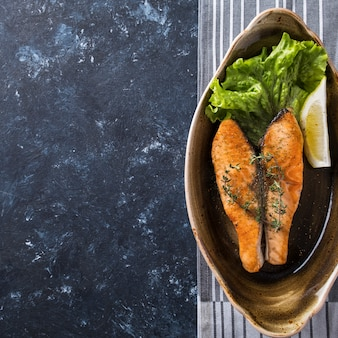 Verdure arrostite della bistecca di color salmone su un piatto. vista dall'alto.