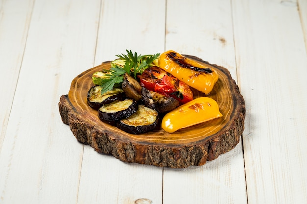 Verdure arrostite e fungo sul bordo di legno