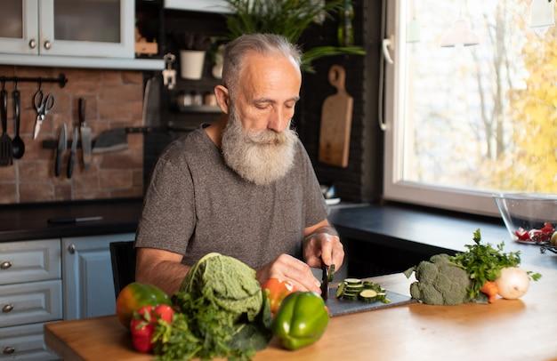 Verdure barbute di taglio dell'uomo senior sul bordo di legno