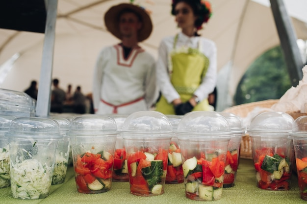 Verdure biologiche in tazze per andare. primo piano di un sacco di bicchieri di plastica riempiti con verdure tritate e insalate sul tavolo al festival del cibo. insalata da asporto e verdure sul tavolo.