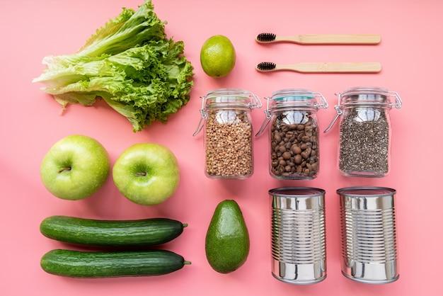 Verdure, cibo in scatola e spazzolini da denti in legno su sfondo rosa