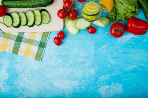 Verdure con piatto vuoto sul panno sul tavolo blu