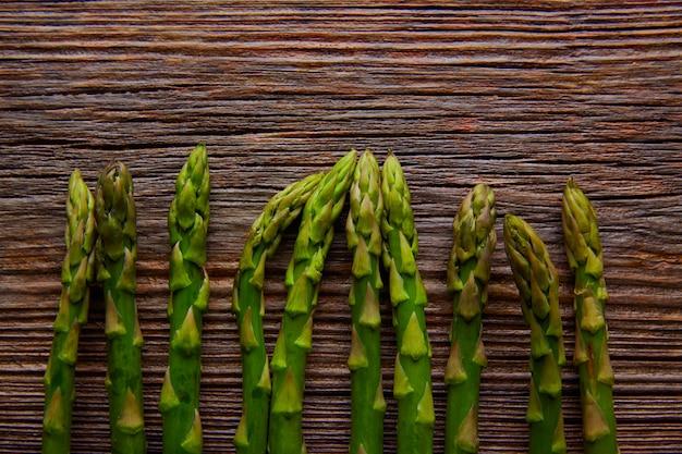 Verdure crude dell'asparago in una fila su legno invecchiato