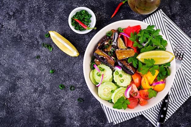 Verdure crude fresche dell'insalata - cetriolo armeno, pomodori, paprica, prezzemolo e melanzane stufate. ciotola di buddha vegana