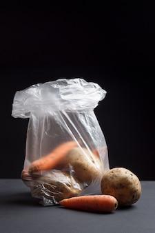 Verdure crude in un sacchetto di plastica. l'immagine mostra gli effetti dannosi dei sacchetti di plastica sul cibo.