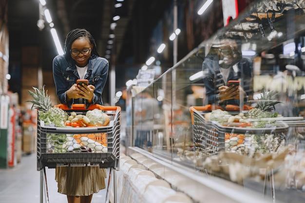 Verdure di acquisto della donna al supermercato